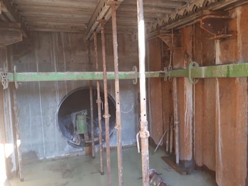 Inside the forebay tank, inlet pipe in back wall  (Props are part of the shuttering for constructing the forebay tank top)