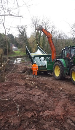 Trough transfer from low-loader to Digger Arm for the downhill slippery journey.